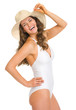 Smiling young woman in swimsuit and hat