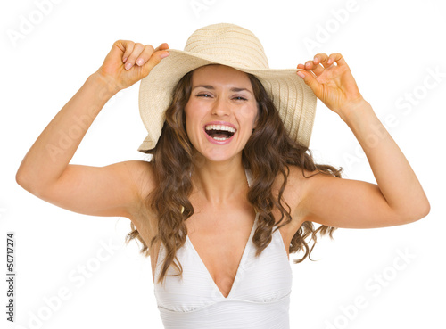 Portrait of smiling young woman in swimsuit and hat