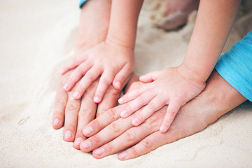 Father and daughter hands on sand