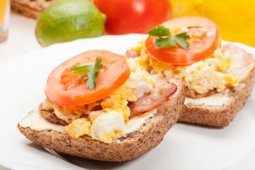 Sandwich with scrambled eggs and bacon. Selective focus.