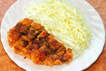 Tonkatsu. Japanese pork cutlet with cabbage on white plate.