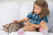 Cute little girl hugging tabby cat with love, looking at cat.