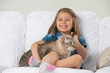 Cute little girl hugging tabby cat with love, looking away.