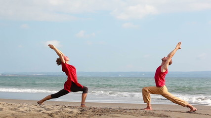 Peaceful pair practicing yoga together on beach