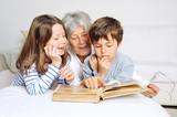 Oma schaut mit Enkelkindern ein Fotoalbum an