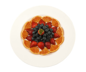 plate full of fresh fruit-orange,strawberries and blueberries