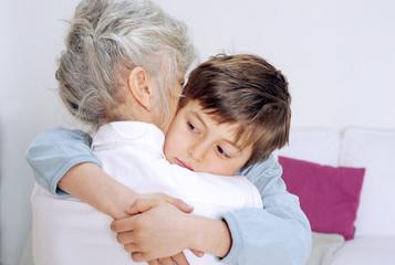 Kind wird von Oma getröstet