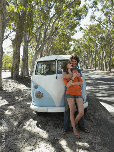 Young couple embracing leaning against front of camper van parked by road