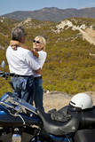 Senior couple embrace next to motorcycle in the desert