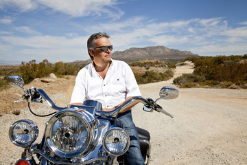 Senior man wearing sunglasses on motorcycle in desert