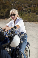 Senior woman smiling and sitting on motorcycle in desert