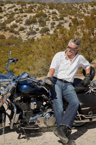 Senior man leans on motorcycle in desert