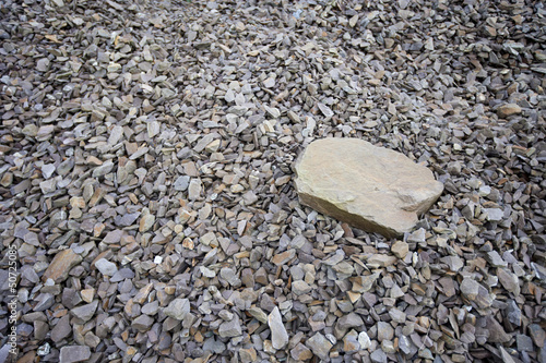 Large rock sitting on pile of smaller rocks