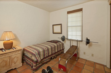 Small single bedroom with bench press and weights