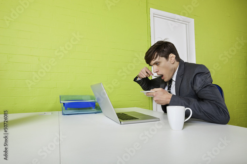 Side view of young businessman eating while using laptop at table