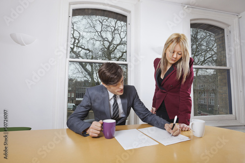 Young businesswoman looking at male colleague signing documents at conference table