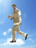 Business running whilst checking wristwatch in mid-air against cloudy sky