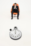 Anxious businessman sitting on chair with stopwatch in front of him representing loss of time