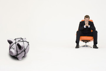 Pensive businessman on chair and piggybank tied with rope representing financial difficulties
