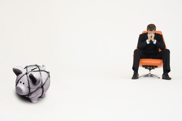 Worried businessman on chair and piggybank tied with rope representing financial difficulties