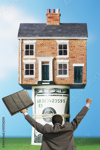 Back view of victorious businessman with briefcase in front of house on money rolls