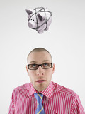 Young businessman looking up at piggy bank tied with rope representing trapped finances