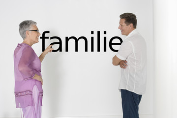"Couple discussing family issues against white wall with German text ""Familie"""