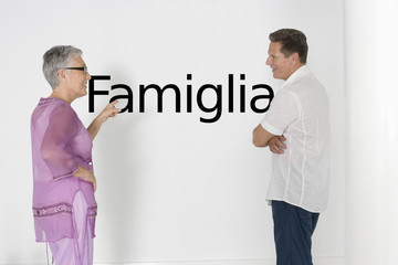 """Couple discussing family issues against white wall with Italian text """"Famiglia"""""""