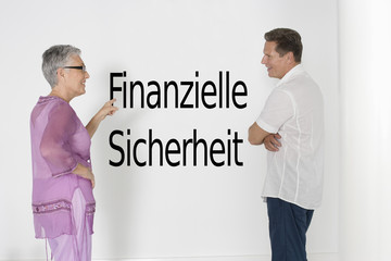 "Couple discussing financial security against white wall with German text ""Finanzielle Sicherheit"""