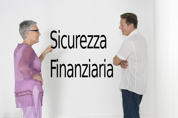 "Couple discussing financial security against white wall with Italian text ""Sicurezza Finanziaria"""
