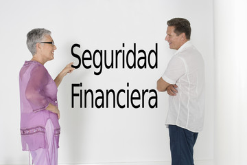 "Couple discussing financial security against white wall with Spanish text ""Seguridad Financiera"""