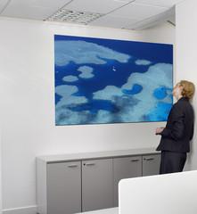 Contemplative young businesswoman looking at painting on wall in office