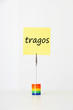 "Sticky notepaper with Spanish text ""Tragos"" (Drinks) clipped to a multicolored card holder"