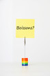 "Sticky notepaper with French text ""Boissons?"" (drinks) clipped to a multicolored card holder"