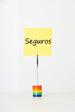 "Sticky notepaper with Spanish text ""seguros"" (Insurance) clipped to a multicolored card holder"