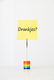 "Sticky notepaper with Dutch text meaning ""Drankjes?"" (Drinks) clipped to a multicolored card holder"