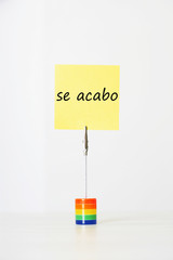 "Sticky notepaper with Spanish text ""se acabo"" (It's over) clipped to a multicolored card holder"