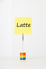"Sticky notepaper with Italian text ""latte"" (milk) clipped to a multicolored card holder"