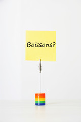 """Sticky notepaper with French text """"Boissons?"""" (drinks) clipped to a multicolored card holder"""