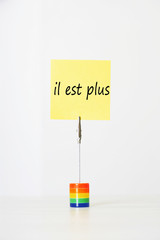 "Sticky notepaper with French text ""il est plus"" (It's over) clipped to a multicolored card holder"