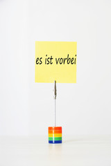 "Sticky notepaper with German text ""es ist vorbei"" (It's over) clipped to a multicolored card holder"