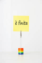 Sticky notepaper with Italian text meaning It's over clipped to a multicolored card holder