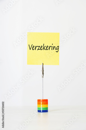 "Sticky notepaper with Dutch text ""Verzekering"" (Insurance) clipped to a multicolored card holder"
