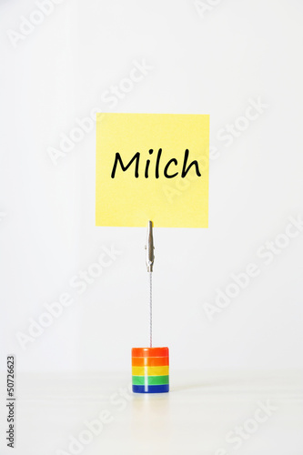 "Sticky notepaper with German text ""Milch"" (milk) clipped to a multicolored card holder"