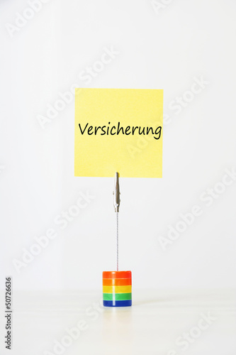 "Sticky notepaper with German text ""Versicherung"" (Insurance) clipped to a multicolored card holder"