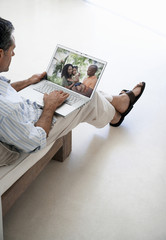 Middle-aged man browsing through family photographs on laptop at home