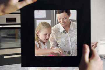 Female hand framing mother and daughter baking together in kitchen