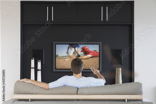 Back view of mid-adult man changing channels with television remote control in living room