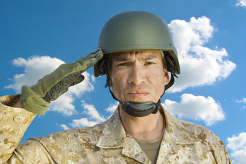 Portrait of middle-aged soldier in military uniform saluting against cloudy sky