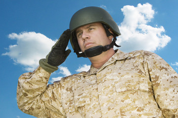 Mid-adult soldier in military uniform saluting against cloudy sky